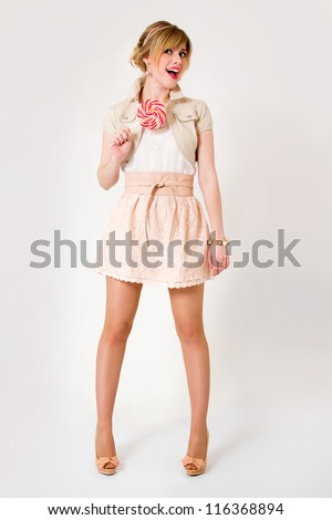 Beautiful girl with big lollipop in full growth - stock photo