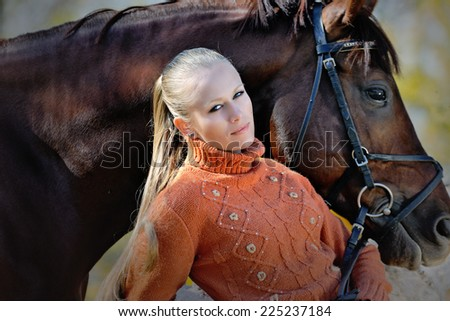 Beautiful girl with blond hair and chestnut horse - stock photo