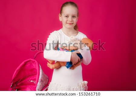 beautiful girl with blond hair holding a doll - stock photo