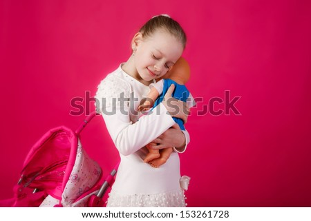beautiful girl with blond hair swayed doll to sleep. close-up - stock photo
