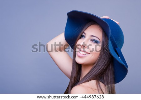 Beautiful girl with blue hat, smiling. Studio shot.