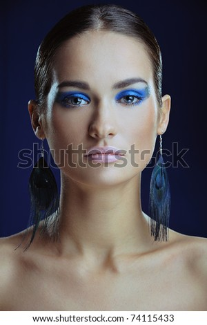 beautiful girl with blue make-up in long earrings - stock photo