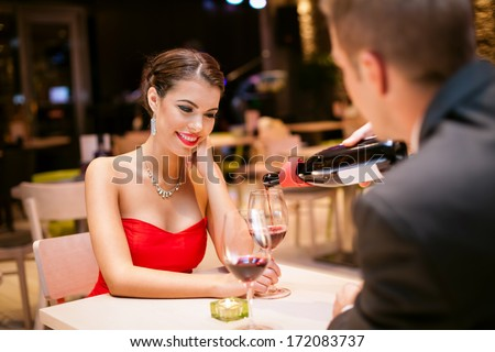 beautiful girl with  boyfriends in restaurant, he pouring wine in her glass