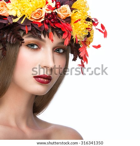 Beautiful  girl with bright autumn wreath of leaves and flowers. Beauty face. Picture taken in the studio on a white background.
