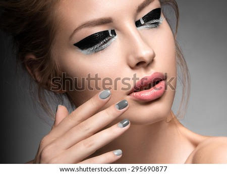 Beautiful girl with bright creative fashion makeup and Grey nail polish. Art beauty design.