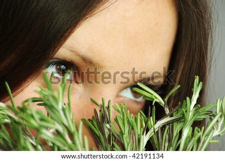 Beautiful girl with bright eyes sniffing rosemary