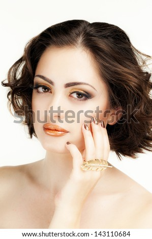 Beautiful girl with bright make-up, gold lips, brown nails with gel nail polish - stock photo