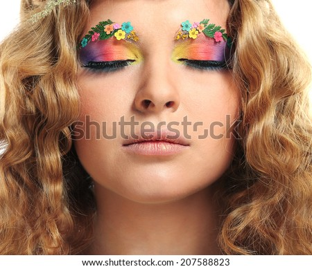 Beautiful girl with bright makeup and eyebrows decorated with flowers. Fantasy girl portrait. Summer fairy portrait. Long permed hair