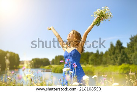 Beautiful girl with bunch of camomiles. countryside
