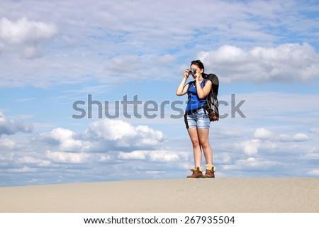 beautiful girl with camera hiking in desert - stock photo