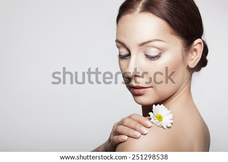 Beautiful Girl With Camomile Flowers.Beauty Woman Face. Perfect Skin. Professional Make-up. - stock photo