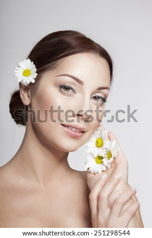 Beautiful Girl With Camomile Flowers.Beauty Woman smiling. Perfect Skin. Professional Make-up. - stock photo