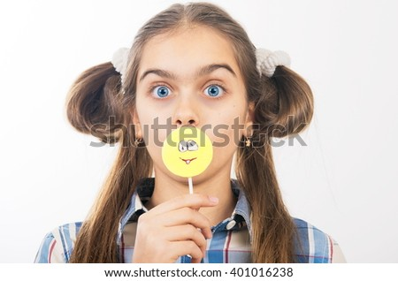Beautiful girl with candy on a stick. Candy in the form of smiley. Girl and sweet. Cheerful teen girl eating candy on Stick, yellow smiley - stock photo