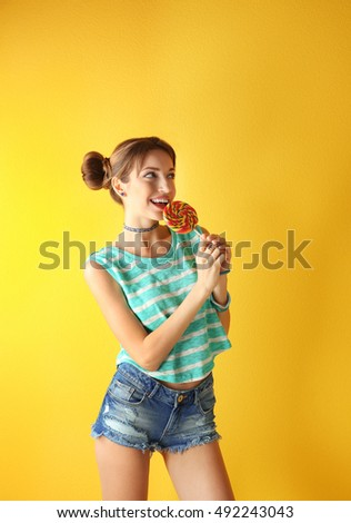 Beautiful girl with candy on yellow background
