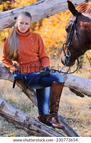 Beautiful girl with chestnut horse in autumn forest - stock photo