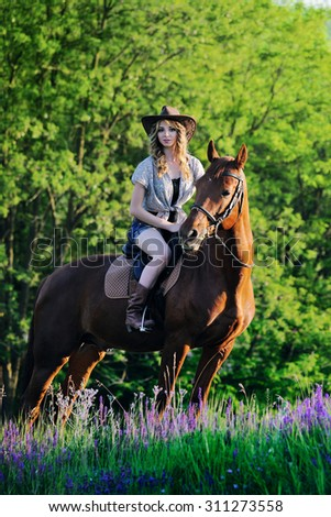 Beautiful girl with chestnut horse in evening field
