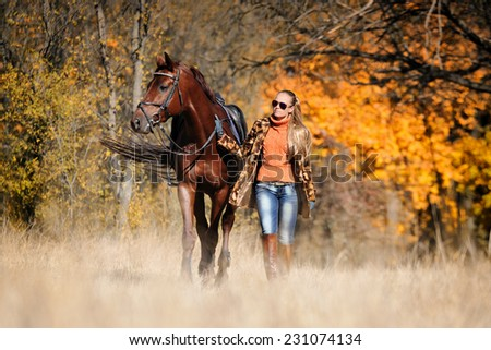 Beautiful girl with chestnut horse in fall - stock photo