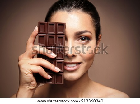 Beautiful girl with chocolate on brown background