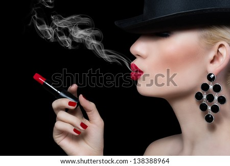 Beautiful girl with cigarette and red lips on black background  - stock photo