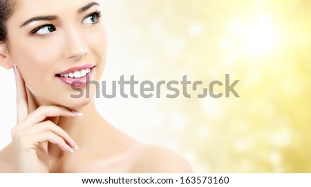 Beautiful girl with clean fresh skin, yellow background with sun