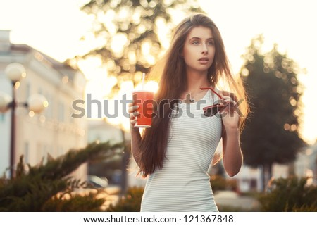 Beautiful girl with cold tankard outdoors - stock photo