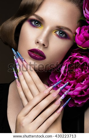 Beautiful girl with colorful make-up, flowers, retro hairstyle and long nails. Manicure design. The beauty of the face.