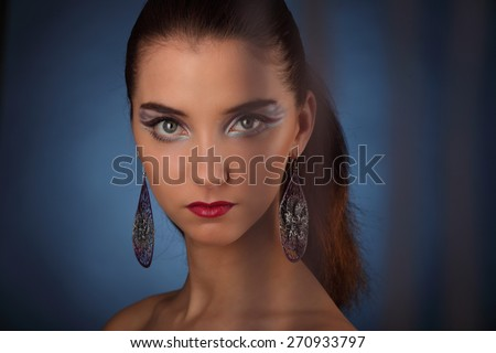 Beautiful girl with creative colorful makeup on a dark background studio