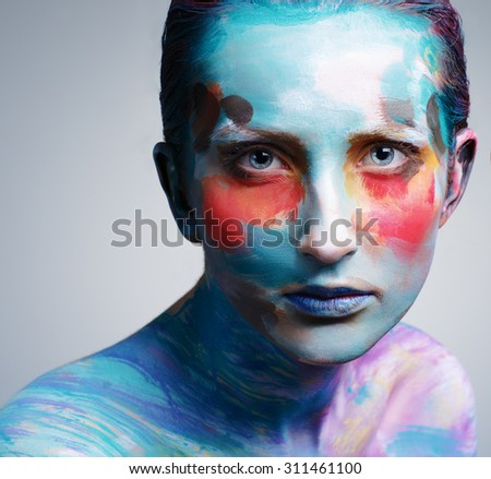 Beautiful girl with creative colorful makeup on a gray background. Beautiful fashion woman color face art. - stock photo
