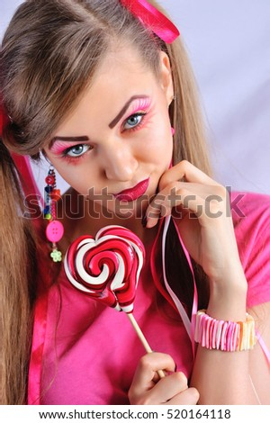Beautiful girl with creative makeup with colorful lollipop