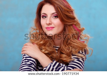 Beautiful girl with curly hair and a pink lock of hair dressed in a striped top posing on a blue background - stock photo