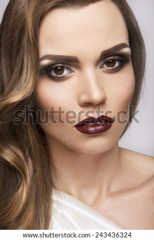 Beautiful girl with curly hair and dark lips.