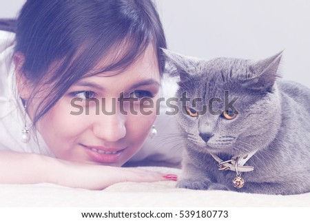 Beautiful girl with curly red hair playing with a gray cat. Toned