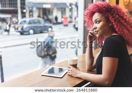 Beautiful girl with curly red hair talking on smart phone in a cafe. Also she is holding a cup of coffee and she has a digital tablet on the table. - stock photo