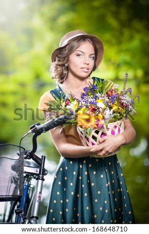Beautiful girl with cute hat and basket with flowers having fun in park with bicycle. Healthy outdoor lifestyle concept. Vintage scenery. Pretty blonde girl with retro look with bike - stock photo