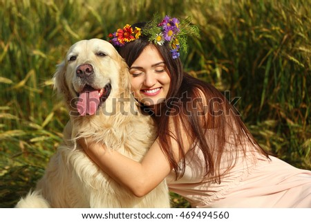 Beautiful girl with cute retriever in field