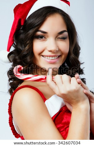 Beautiful girl, with dark curly hair, wearing in red santa costume and hat, holding colorful candy and blinking, on the white background, in studio, close up - stock photo