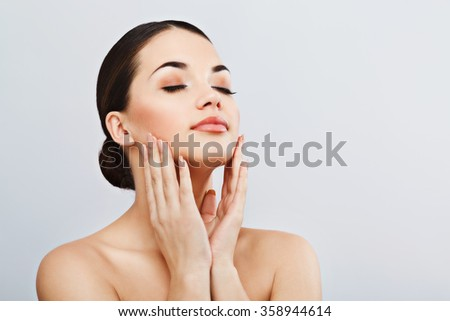 Beautiful girl with dark hair and dark eyebrows, with naked shoulders, touching face with closed eyes, a model with light nude make-up, gray studio background, beauty photo, copy space.  - stock photo