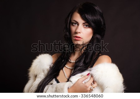Beautiful girl with dark hair in a white fur coat with pearls