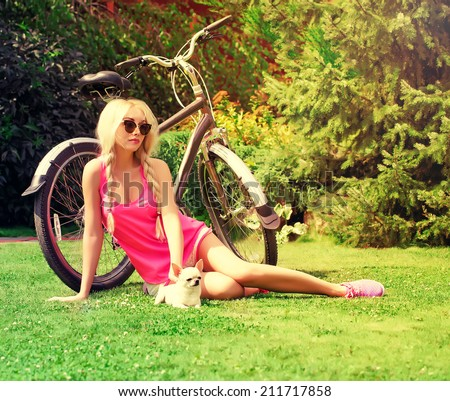 beautiful girl with dog and bicycle in the park . - stock photo