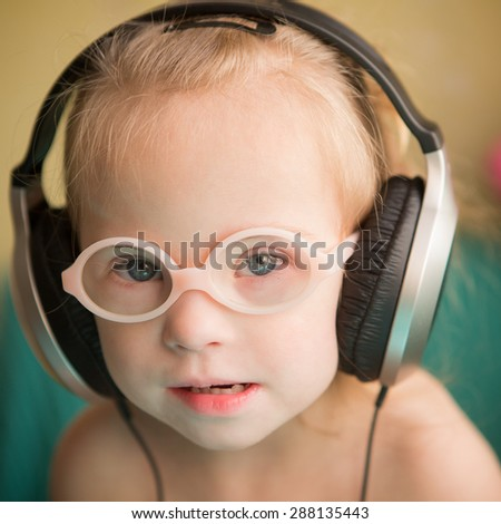 beautiful girl with Down syndrome is listening to music on headphones