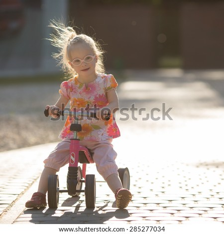 beautiful girl with Down syndrome riding a bike - stock photo