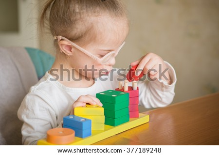 beautiful girl with Down syndrome sorts geometric shapes - stock photo