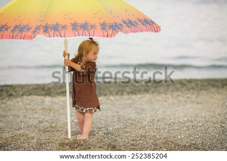 beautiful girl with Down syndrome standing under an umbrella on the beach - stock photo