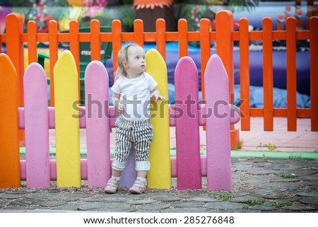 beautiful girl with Down syndrome walks in the park - stock photo
