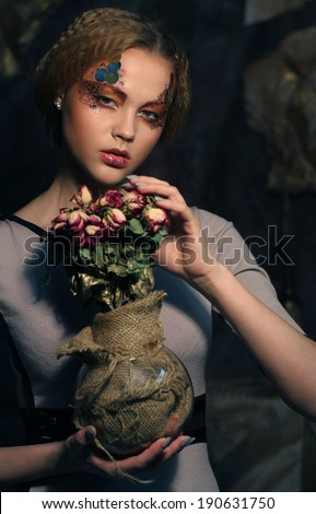 beautiful girl with dry roses in decoration - stock photo