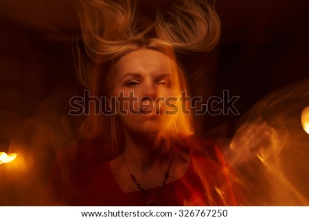 Beautiful  girl with  flame on black background - stock photo