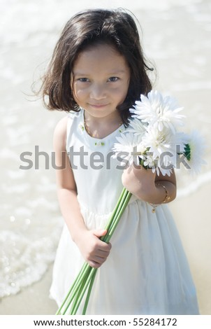 beautiful girl with flower at the beach - stock photo
