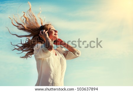 beautiful girl with flying  blond hair, listening to music on headphones in the sky - stock photo