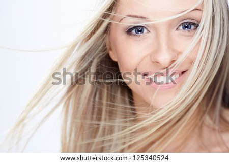Beautiful girl with flying hair on a white background