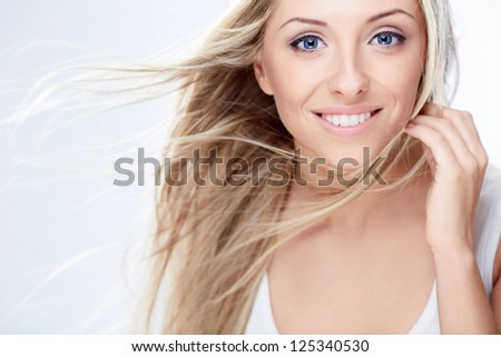 Beautiful girl with flying hair on a white background - stock photo